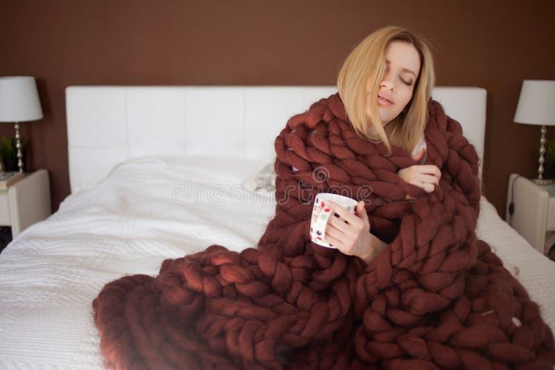 E Mooi meisje in een comfortabele deken stock foto