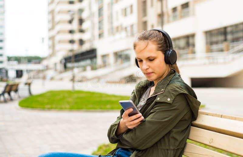 E mujer joven que escucha la m?sica usando el tel?fono m?vil que se sienta en banco fotos de archivo libres de regalías