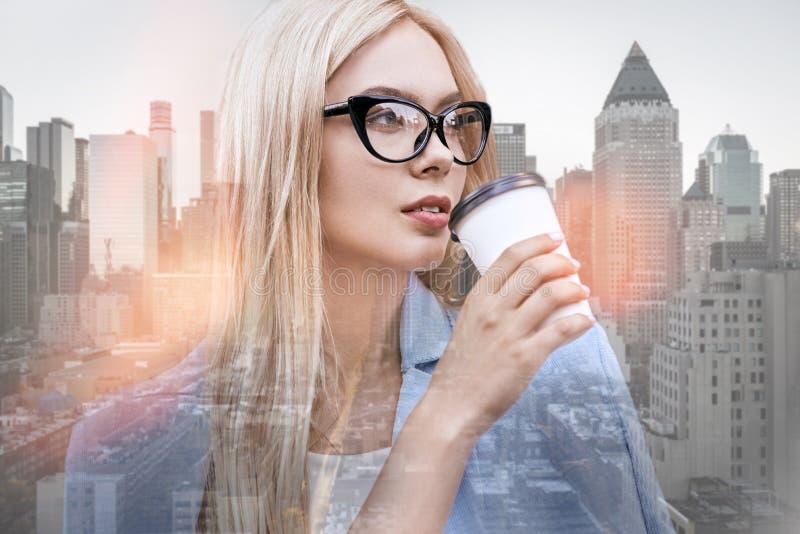 E Nahaufnahmeporträt schöner Geschäftsdame mit trinkendem Kaffee und weg schauen des blonden Haares lizenzfreies stockbild