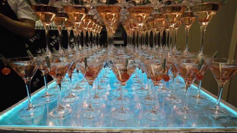 Muitos vidros para Martini com álcool estão na tabela na barra a??o Montanhas de vidros de vinho Martini com alcoólico imagens de stock
