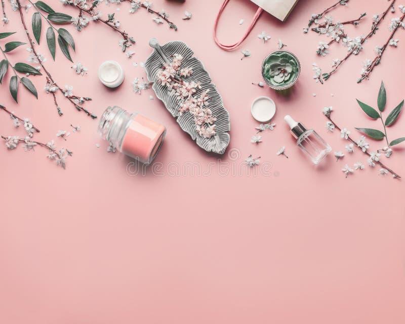 E Olika ansikts- anti--åldras produkter på pastellfärgad rosa bakgrund med den körsbärsröda blomningen och sidor, överkant royaltyfria bilder