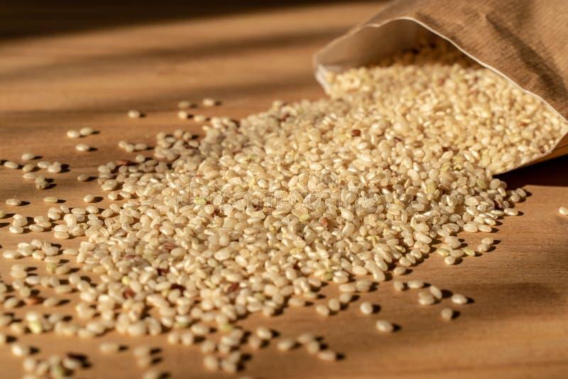 E Organische Ongepelde rijst op a-lijst met Zak op de Achtergrond royalty-vrije stock foto's