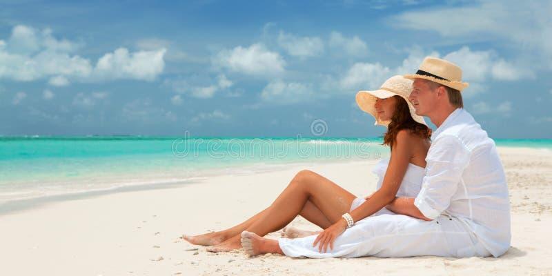 E Par kopplar av p? den vita sanden av stranden Lycklig havslivsstil Den unga familjen, mannen och kvinnan vilar fotografering för bildbyråer