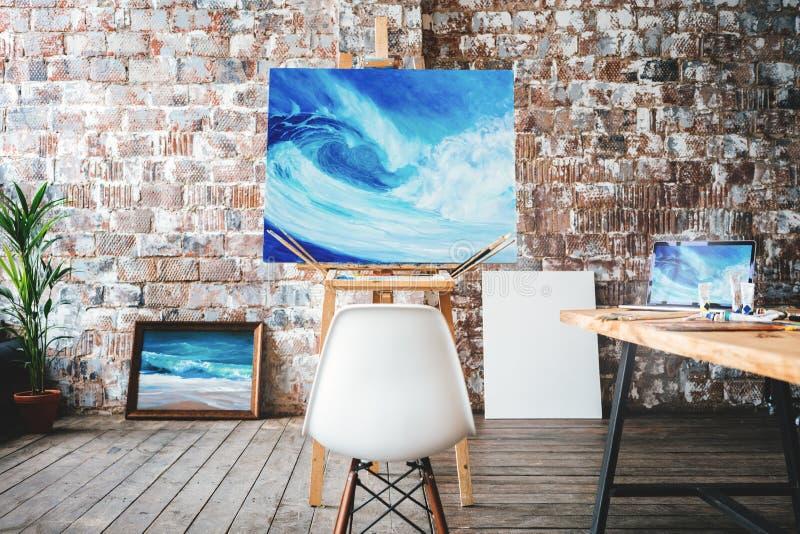 E Pintura en lona en el caballete en el estudio Diversas brochas y pinturas en la tabla de madera imágenes de archivo libres de regalías