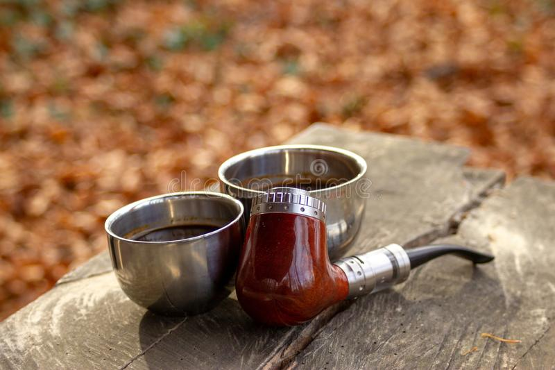 E-pipe with blurred background and cup of coffee in natural ambient stock photo