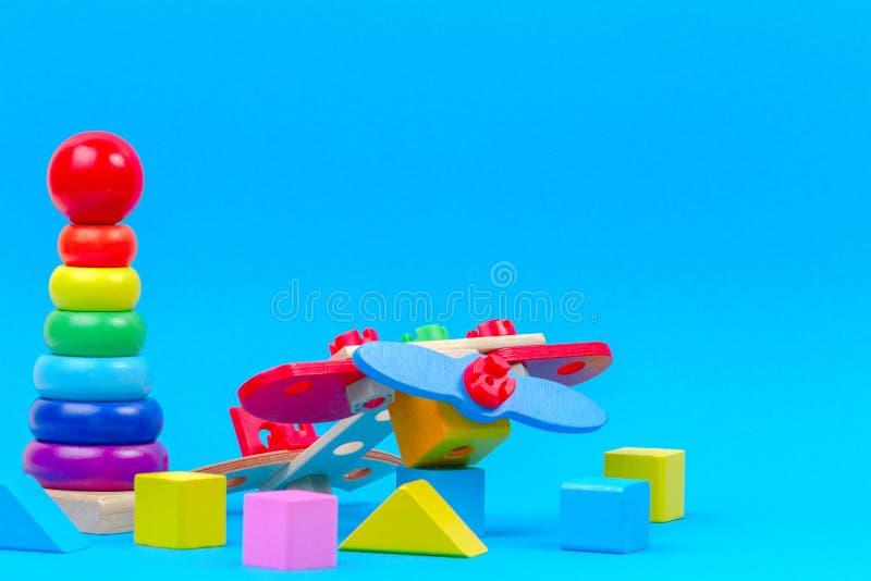 E Plano de madeira do brinquedo, bebê que empilha a pirâmide dos anéis e blocos coloridos no fundo azul imagem de stock