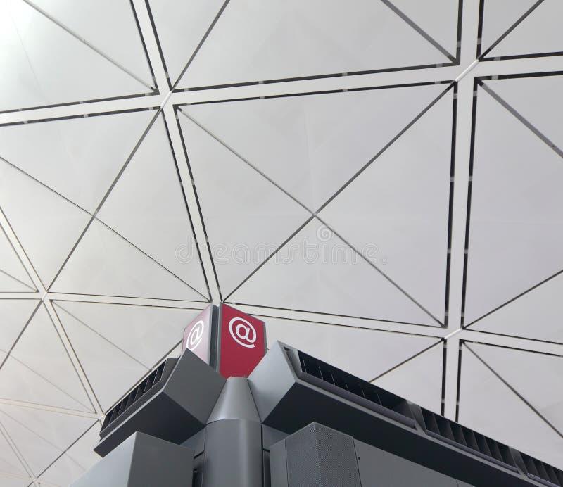 E-postteckensymbol med modern byggnad arkivbild