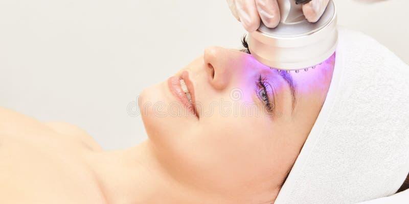 E Procedimiento de la cabeza de la cosmetolog?a Cara de la mujer de la belleza Dispositivo cosm?tico del sal?n Rejuvenecimiento f fotos de archivo libres de regalías