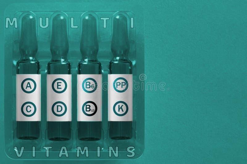 E Quattro ampolle con le lettere della sovrapposizione degli elementi della vitamina di A.C.E D K pp B6 B12 dell'iscrizione immagine stock
