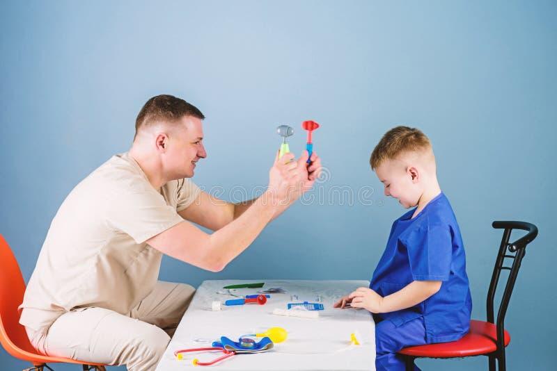 E r Ο γιατρός ατόμων κάθεται τα επιτραπέζια ιατρικά εργαλεία εξετάζοντας τον ασθενή μικρών παιδιών Παιδίατρος στοκ εικόνες