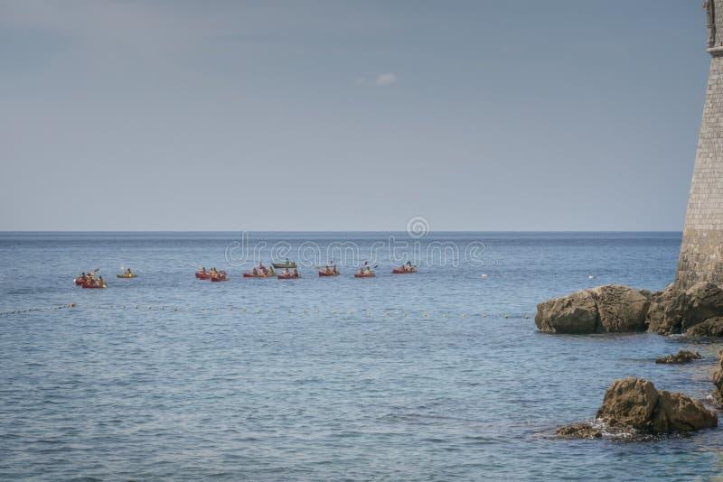 Молодые люди плывут в морских каяках Водоснабжение в Дубровнике Активный отдых на море стоковые фотографии rf