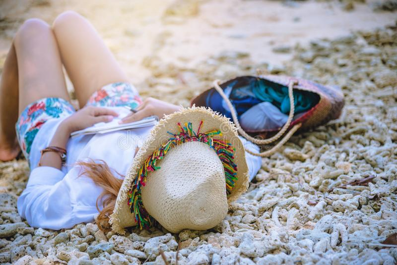 E r Исследование прочитало книгу Образование природы пишет примечание Сон на пляже r стоковая фотография