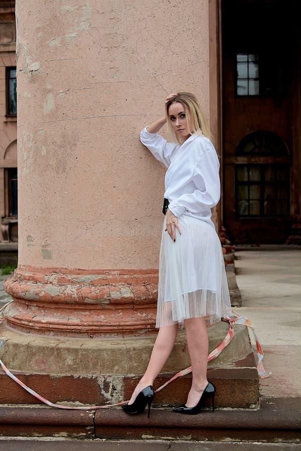 Женщина модного вида Современный портрет молодой женщины Молодая женщина, одетая в белую юбку и одетая в рубашку и позирующая на  стоковые изображения