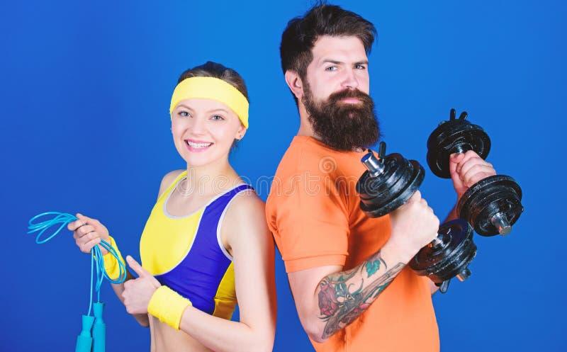 E r 与杠铃和跳绳的运动的夫妇训练 i 免版税库存照片