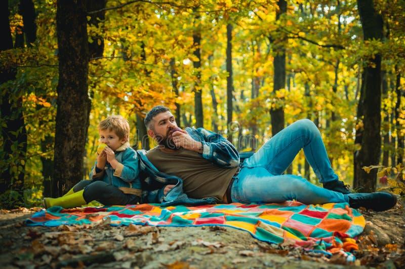 健康小吃 家庭野餐 有儿子的潮人蓄胡子的爸爸,在森林里度过 库存图片