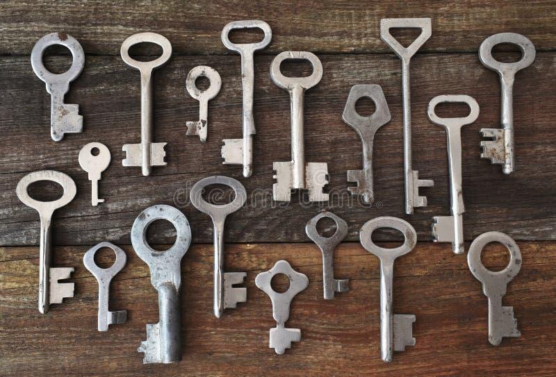 旧的复古钥匙图案 古董金铜银色挂锁的不同线索 位于棕色木 库存图片