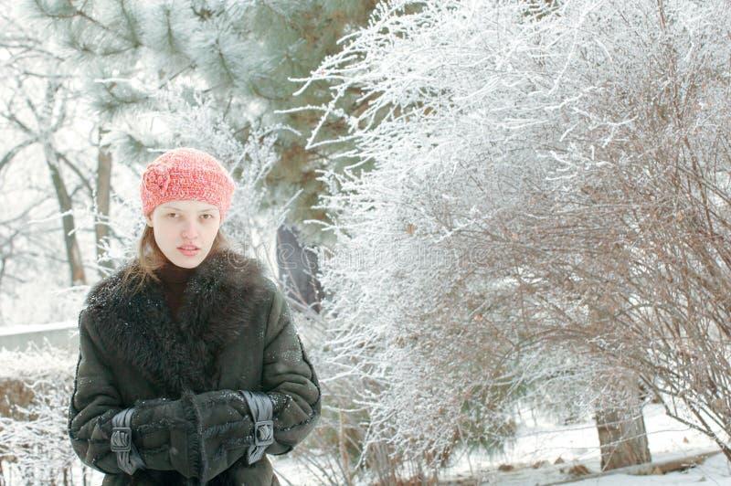 Молодая красивая девушка позирует для фотографа и флиртует с ним, показывая ему свое милое молодое тело Жакет волчьего меха стоковая фотография rf
