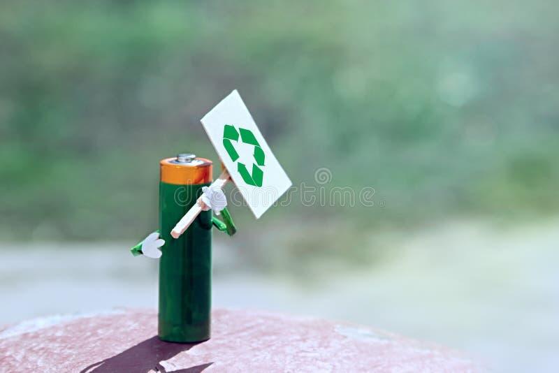 Använd den humaniserade figuren av AA-batteriet i handaffisch med återcirkuleringsikon Anmodan om korrekt bortskaffande separat s royaltyfri foto