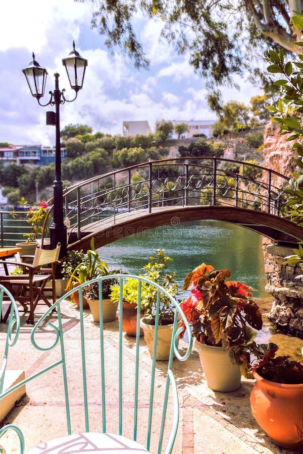 Kaffeehaus im romantischen Stil Charmanter Garten des Cafés mit stilvollem Dekor Seebrücke, Metallstuhl, Laterne und Pflanzen lizenzfreie stockfotografie