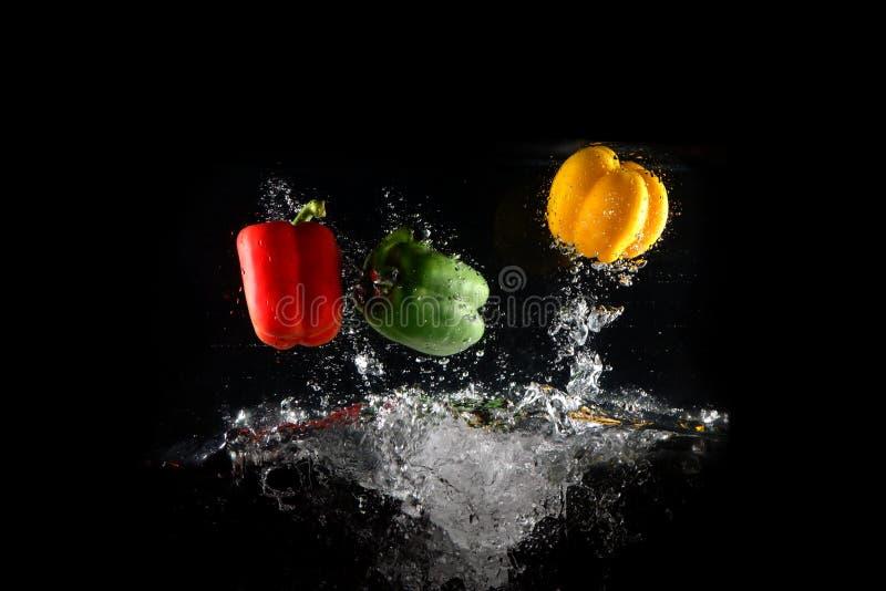 Poivrons verts, jaunes et rouges frais avec éclaboussure d'eau et bulle isolés. Espace de copie coloré. Paprika colorée tombé photographie stock