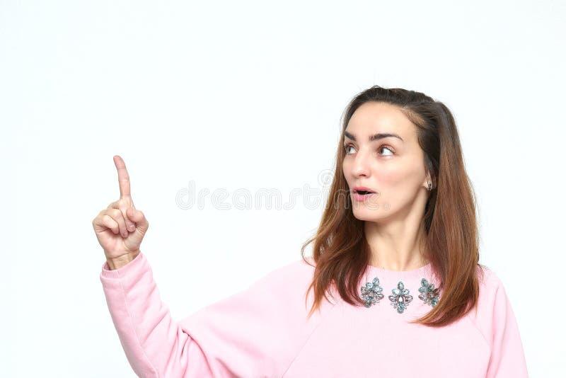 En vacker och överraskad ung kvinna med mörkt hår ser bort och hon har en idé i en rosa jumper Öppna mun och peka uppåt arkivbild