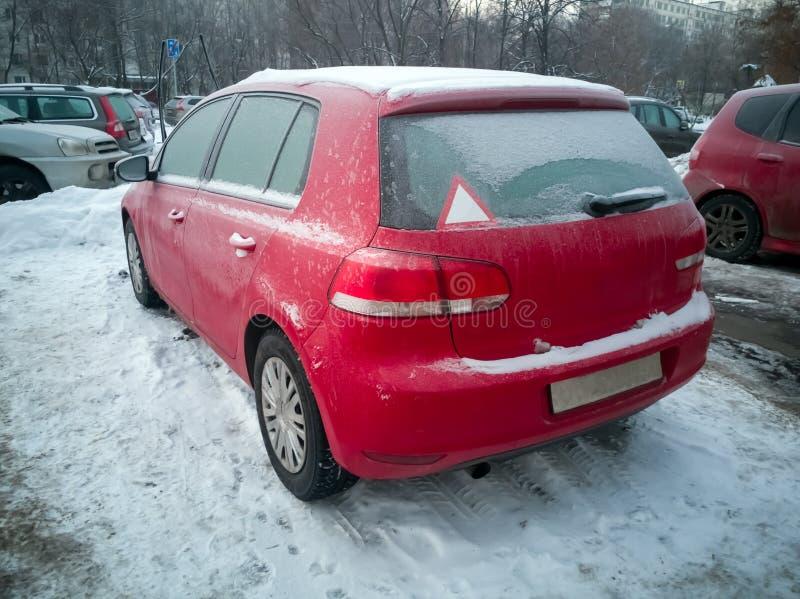 Röd bil under snön Hatchback, fryst, på snö Vinterproblem med att värma upp bilen arkivfoton