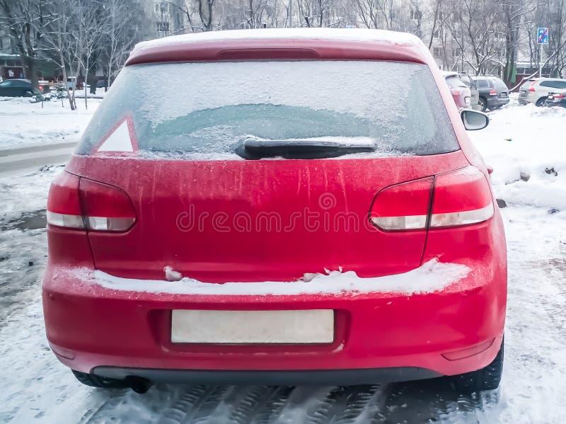 Röd bil under snön Hatchback, fryst, på snö Vinterproblem med att värma upp bilen fotografering för bildbyråer