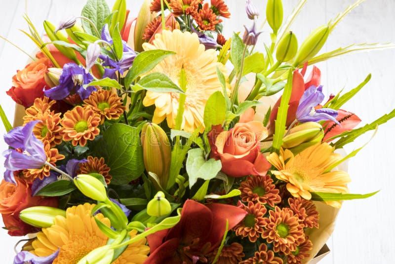 与玫瑰、红色百合、大丁草、大丽花和叶子的花束 免版税库存图片