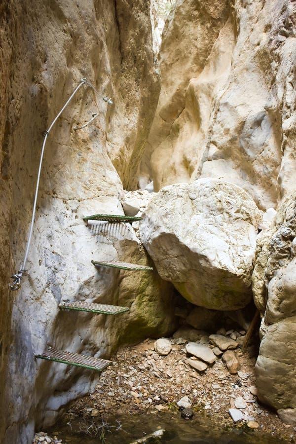 接近攀登山的墙壁的一块垂直的白色石头的一些绿色步帮助对徒步旅行者的保存空白得到 免版税库存图片