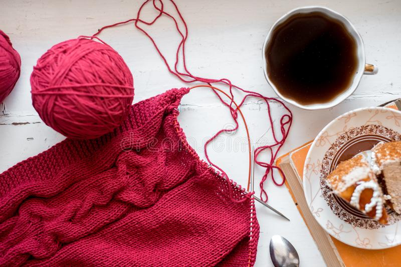 一切都是为了做针线:红线,针织,针织针在木灰色的木制桌子上 顶视图 失败 复制空间 库存照片