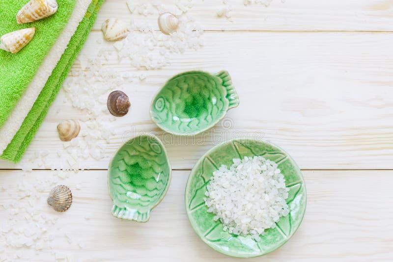 Aromatisch zeezout, zeeschalen en handdoeken Concept voor kuuroorden, schoonheid en gezondheidssalons Sluit foto op witte houten  stock afbeeldingen