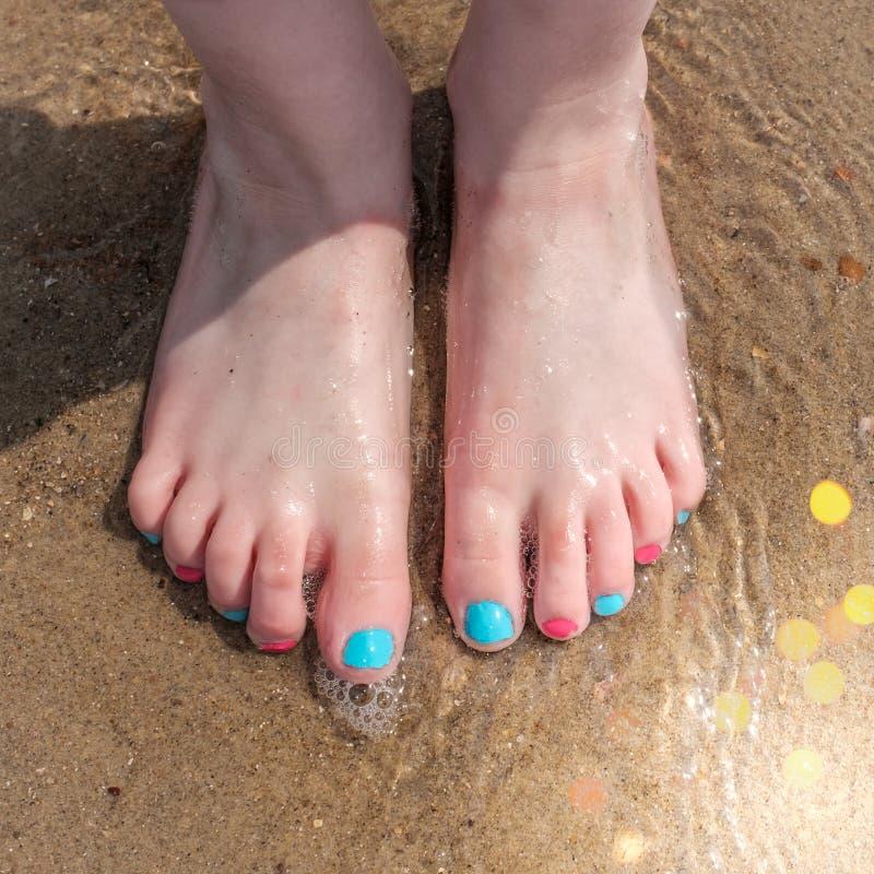 Voeten van een jong meisje die zich op een zandig strand dichtbij de water'srand bevinden stock afbeeldingen
