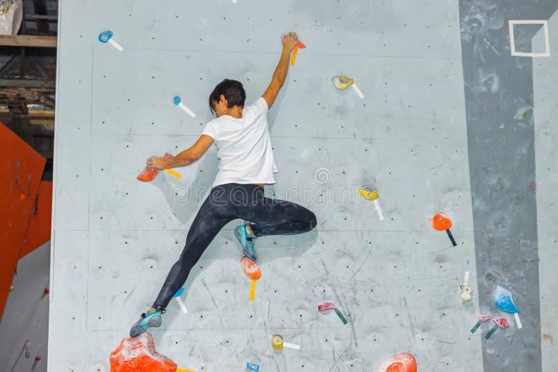垂悬在bouldering的上升的墙壁上的攀岩运动员妇女,里面在色的勾子 免版税库存照片