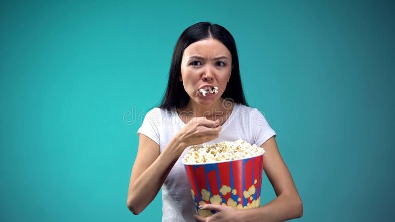 集中于从大纸杯的电影妇女吞食的玉米花,不健康吃 图库摄影