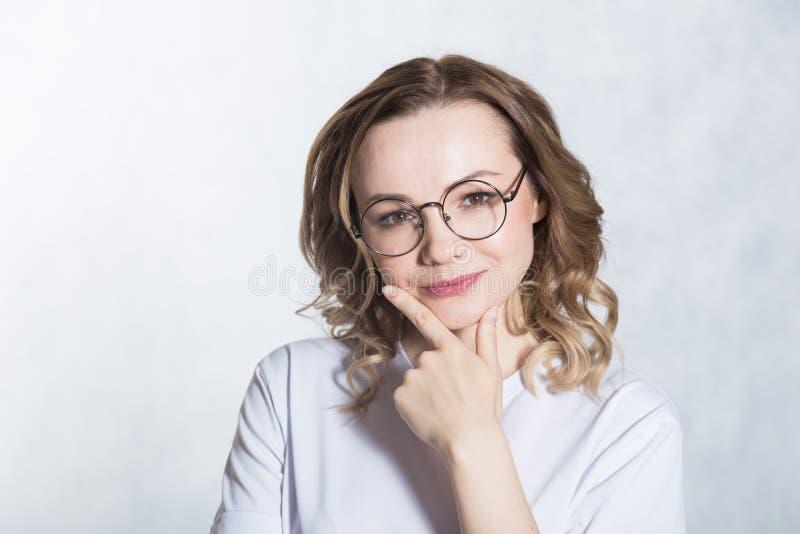戴眼镜的微笑的美丽的年轻女人握她的下巴,看,设法做出决定 库存照片
