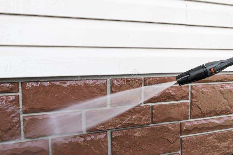 带压力水的清洁服务洗涤建筑物外墙 高压水射流清洗脏墙 电源清洗 免版税库存照片