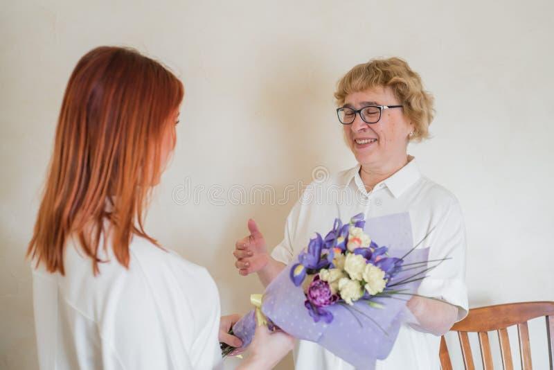 女儿给成年母亲送花 女儿送花给母亲抱抱 共度时光,庆祝 库存图片