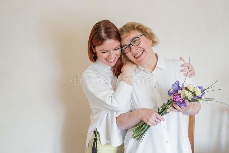 女儿给成年母亲送花 女儿送花给母亲抱抱 共度时光,庆祝 图库摄影