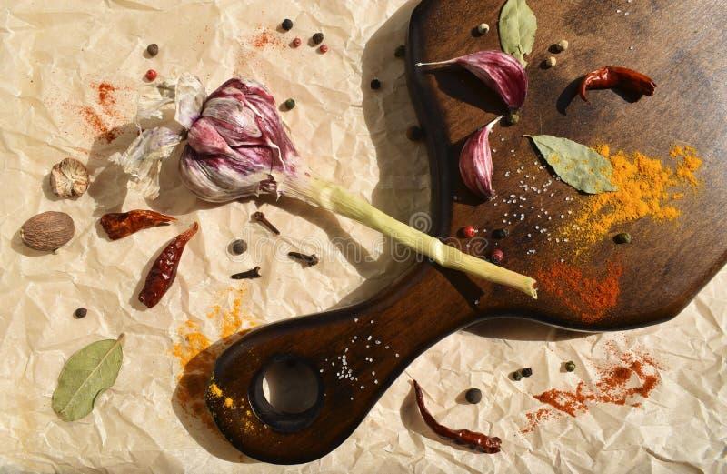 用于在木板上梳理晚餐菜肴的大蒜和各种香料 黑木,月桂叶,辣椒,肉豆蔻 顶部 图库摄影