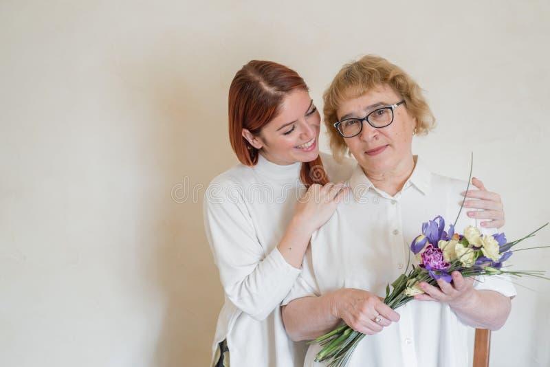 女儿给成年母亲送花 女儿送花给母亲抱抱 共度时光,庆祝 免版税库存照片