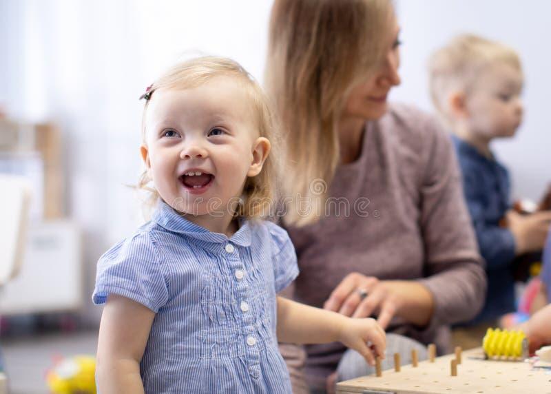 Bebês no jardim de infância Crianças de tenra idade no infantário Pequenas pré-escolas para crianças brincam com professores fotografia de stock royalty free