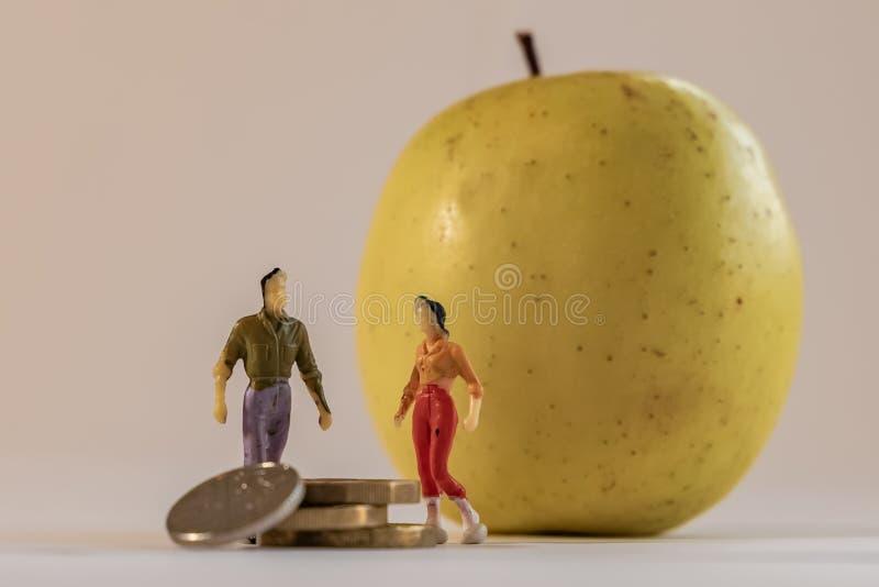 Миниатюрная женщина и мужчина стоят рядом с большим желтым яблоком и считая монеты Уменьшить глубину фона поля Семья стоковые фото