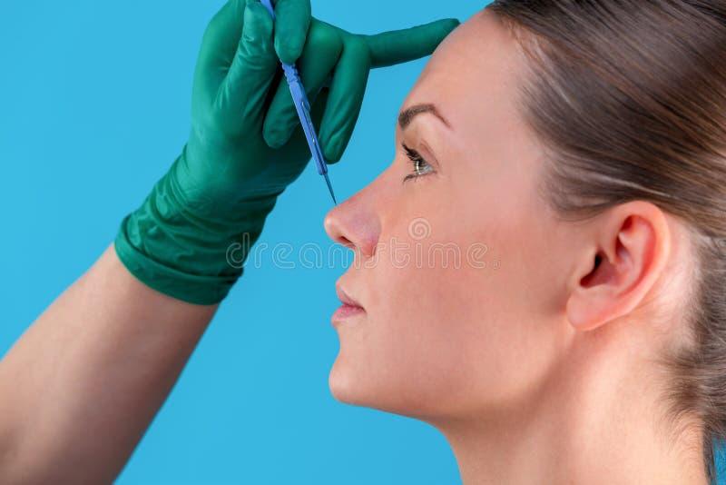 Αισθητικός σχεδιάζει γραμμές διόρθωσης στο πρόσωπο της γυναίκας Πριν από πλαστική χειρουργική οπή Απομονωμένο στο μπλε στοκ εικόνες