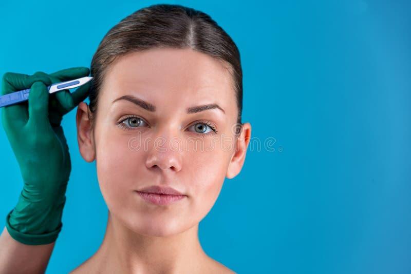 Αισθητικός σχεδιάζει γραμμές διόρθωσης στο πρόσωπο της γυναίκας Πριν από πλαστική χειρουργική οπή Απομονωμένο στο μπλε στοκ εικόνα με δικαίωμα ελεύθερης χρήσης