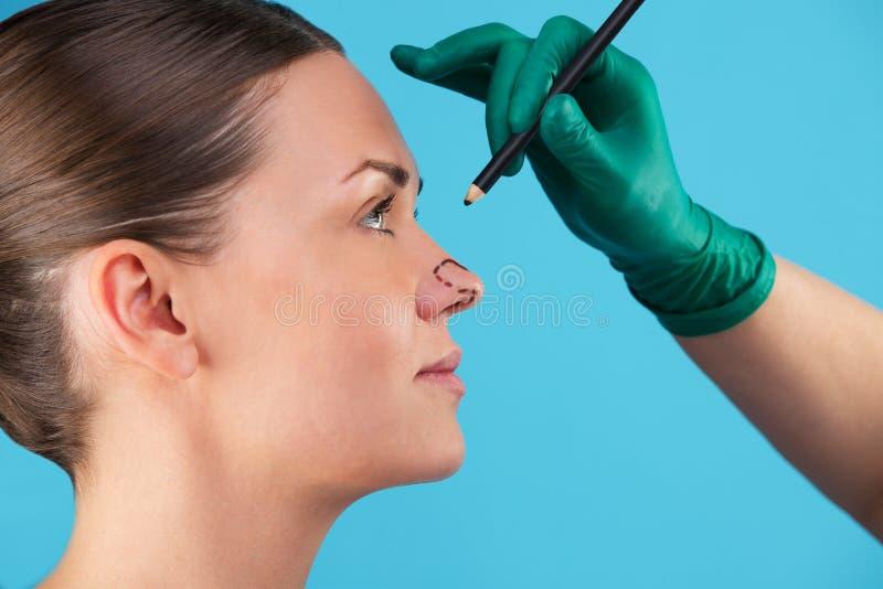 Αισθητικός σχεδιάζει γραμμές διόρθωσης στο πρόσωπο της γυναίκας Πριν από πλαστική χειρουργική οπή Απομονωμένο στο μπλε στοκ φωτογραφία με δικαίωμα ελεύθερης χρήσης