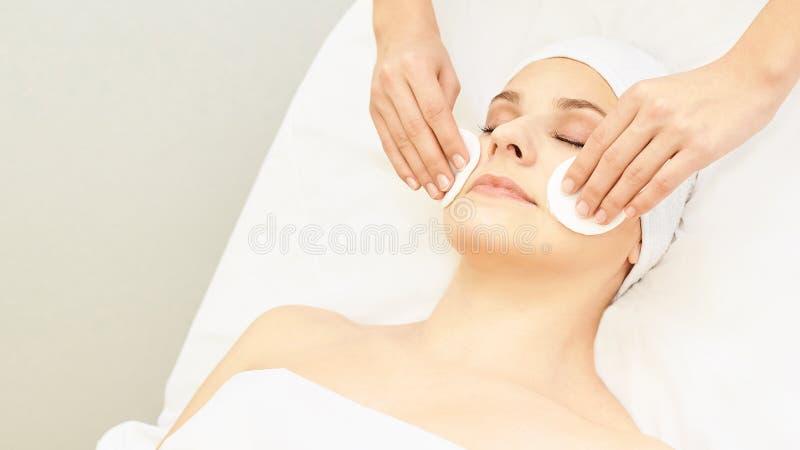 El doctor de Cosmetología retira el ramo de la cara de la chica Almohadilla de algodón con manos femeninas Loción de la demostrac fotografía de archivo libre de regalías
