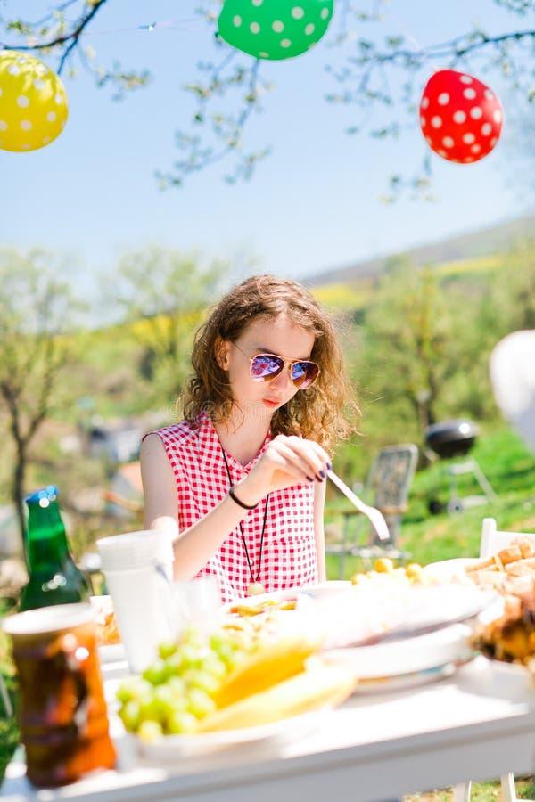 Tonårig åldrig flicka i den röda rutiga skjortan som sitter vid tabellen på trädgårdpartiet royaltyfri bild