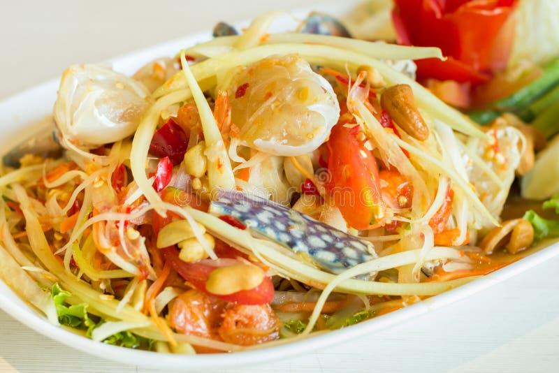 与领域螃蟹的泰国番木瓜沙拉在石桌上的白色盘 免版税库存图片