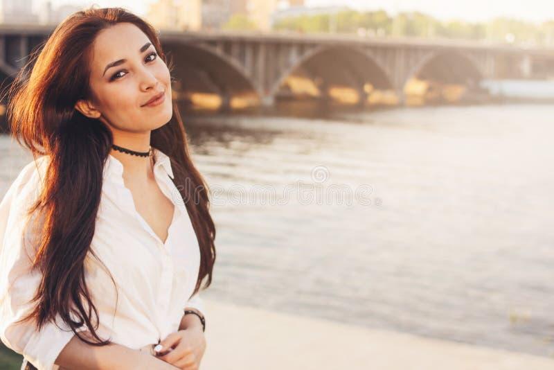 正面美丽的白色衬衫的长发愉快的亚裔女孩在城市河桥梁背景,夏天旅行休假 免版税库存图片