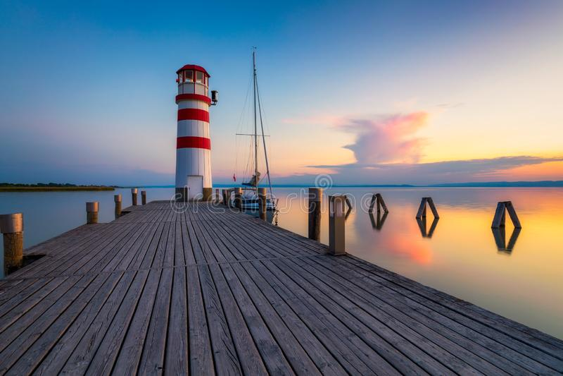 奥地利布尔根兰Podersdorf am See的Lake Neusiedl湖灯塔 奥地利日落灯塔 带灯塔的木制码头 免版税库存照片